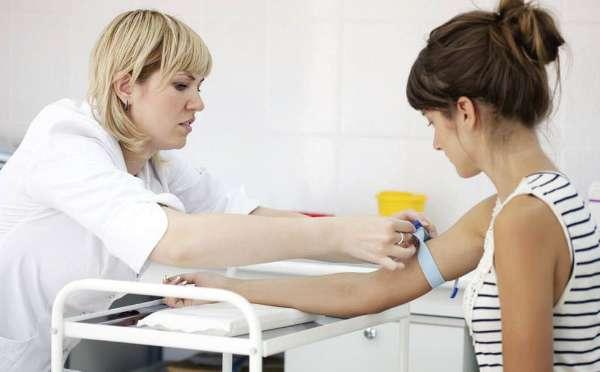 На фото женщина сдает анализы для ЭКО по ОМС.