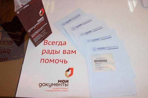 На фото рекламный буклет МФЦ с предложением сменить полис ОМС.