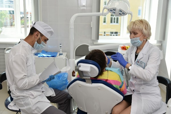 На фото стоматолог лечит ребенка по полису ОМС.
